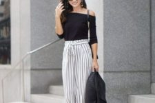 With black off the shoulder top, black leather jacket and heels