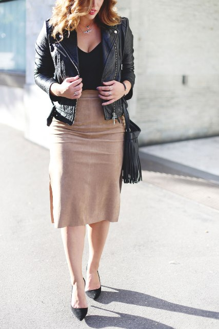 With black top, black leather jacket, fringe bag and pumps