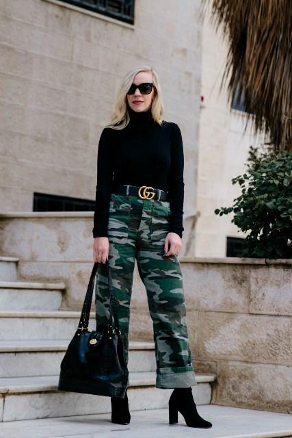 With black turtleneck, belt, black bag and black boots