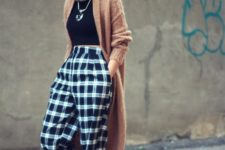With black turtleneck, brown maxi cardigan and white shoes