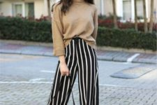 With camel sweater, white sneakers and black and white bag