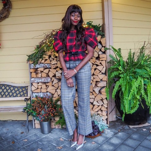 With plaid blouse and silver pumps