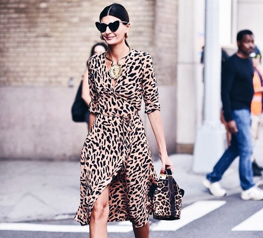 With unique sunglasses and leopard bag