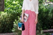 With white button down loose shirt, wide brim hat, three colored bag and white flat mules