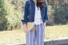 With white ruffled blouse, denim jacket, straw clutch and flat shoes
