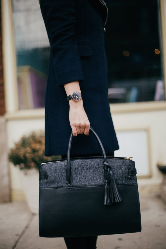 a stylish black leather tote with a tassel is a very comfy and classic item for work
