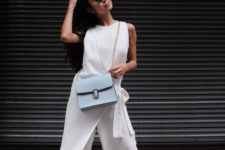 02 a white sleeveless jumpsuit with cropped pants and a wrap detail, white sneakers and a blue bag for a more relaxed feel