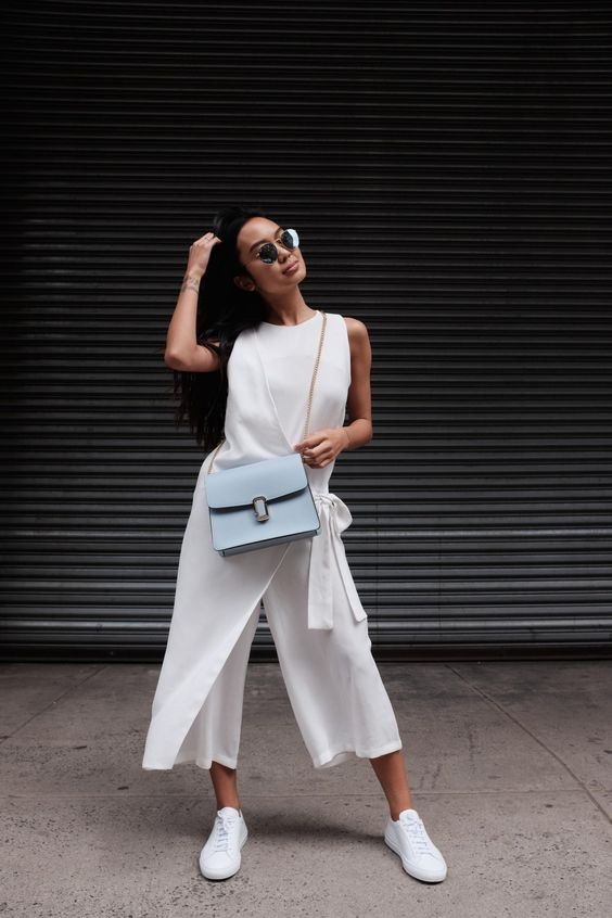 a white sleeveless jumpsuit with cropped pants and a wrap detail, white sneakers and a blue bag for a more relaxed feel