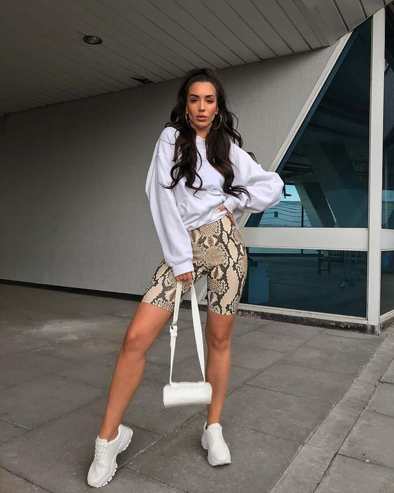 a white sweatshirt, snake print bike shorts, white trainers and a small white bag