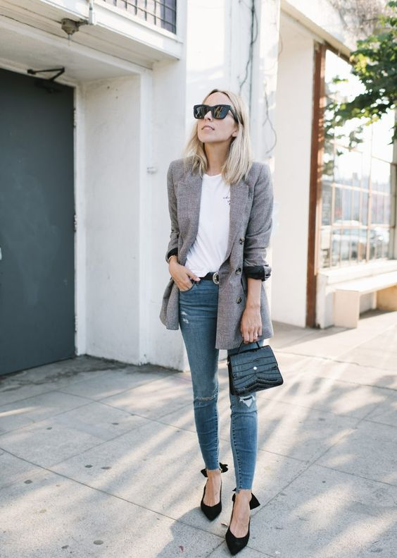 blue ripped skinnies, a white tee, black bow heels, a black bag and a grey oversized blazer
