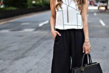 03 a monochromatic work outfit with blakc culottes, a white geometric print sleeveless top, black heels and a black bag