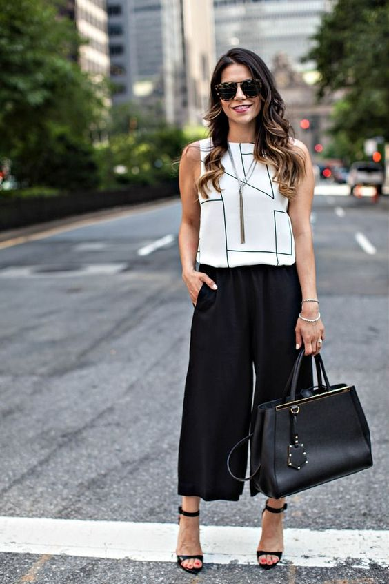 a monochromatic work outfit with blakc culottes, a white geometric print sleeveless top, black heels and a black bag
