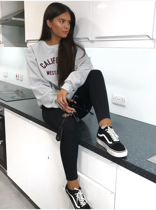 black skinnies, a grey printed sweatshirt, black Vans shoes for a trendy look