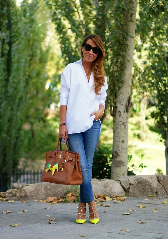 blue cropped jeans, a white shirt, neon yellow spiked shoes for an accent and a brown bag