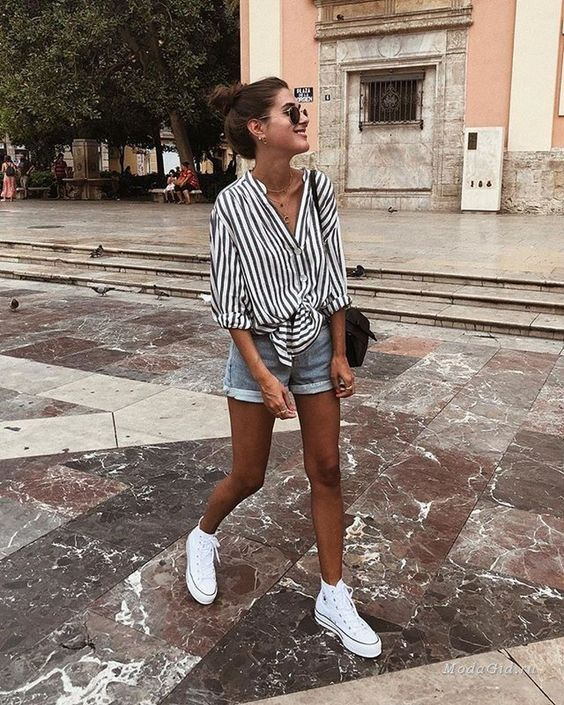 mini denim shorts, a striped black and white oversized button down, white sneakers and a black bag
