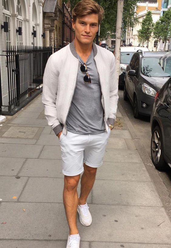 white trainers, a grey tee, a neutral bomber blazer and white shorts for a preppy summer look