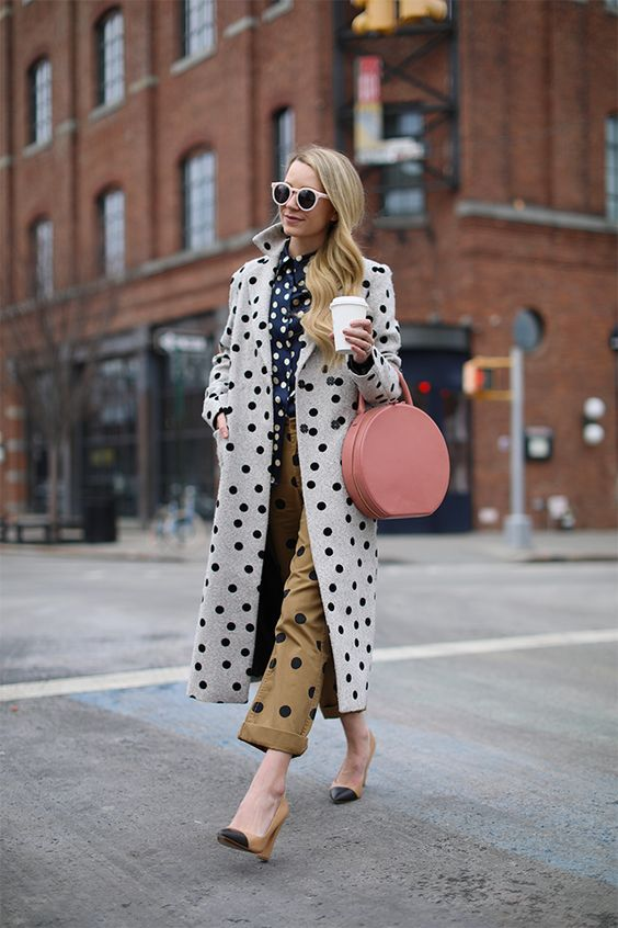 a total polka dot look with a navy and white blouse, camel and black polka dot pants, a coat, a pink round bag and nude and black heels