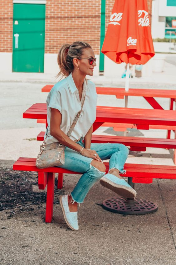 an oversized white button down with short sleeves, blue jeans, white espadrilles and a printed crossbody