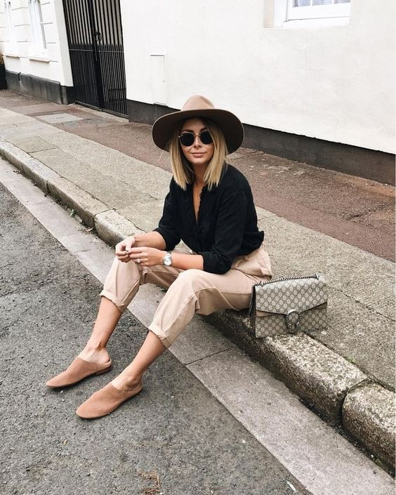 beige camel chino pants and a black button down shirt paired with a fedora hat and a grey bag