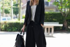 05 a black pantsuit with culottes, a grey tee, black heels and a black backpack for a casual feel