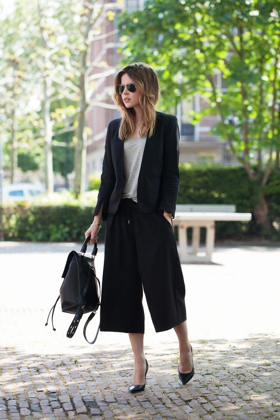 a black pantsuit with culottes, a grey tee, black heels and a black backpack for a casual feel