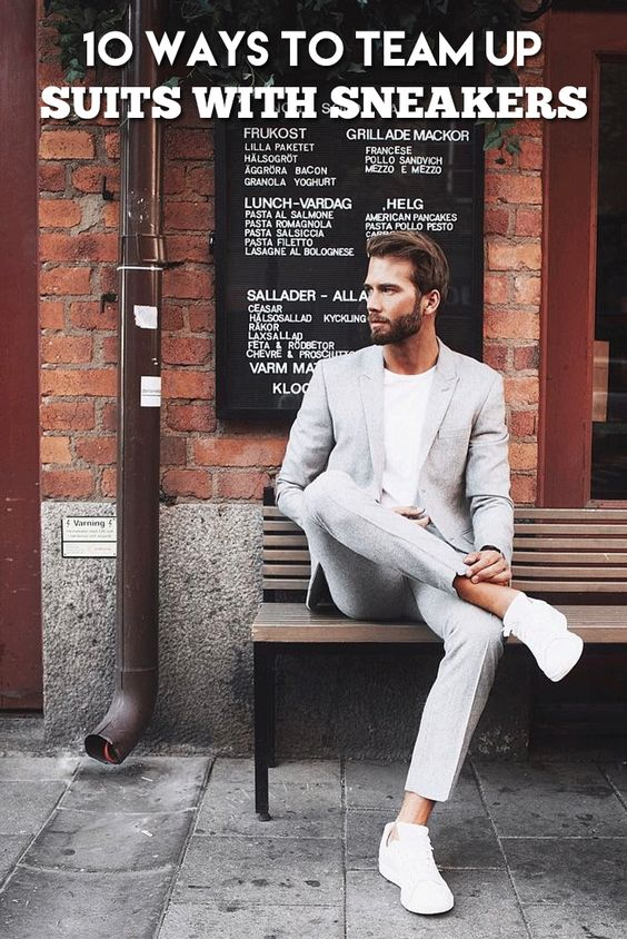 a dove grey suit, a white tee and white trainers with no socks compose a work-appropriate outfit