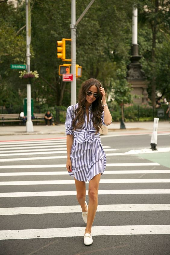 a striped navy and white shirtdress over the knee with a bow and white loafers for an effrotlessly chic look