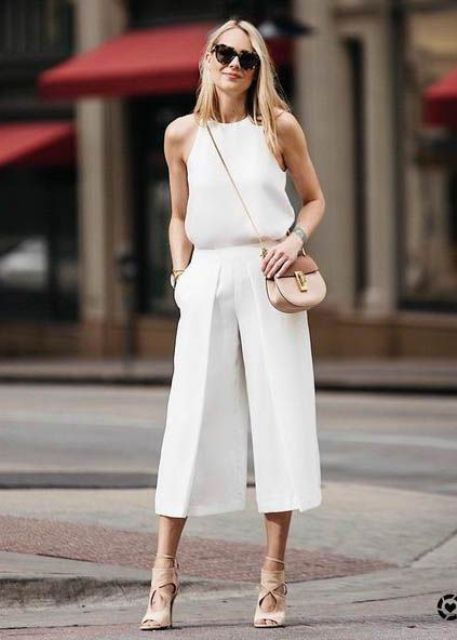a white halter neckline top, white culottes, nude strappy shoes and a nude and camel bag