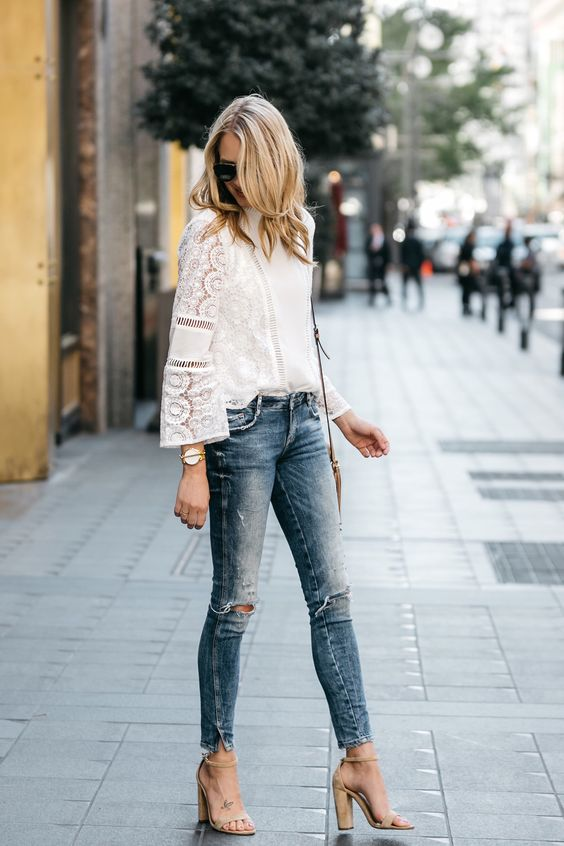 blue skinny jeans, a white crochet lace top with long sleeves, nude block heels and a bag