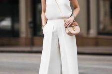 06 a total white look with a halter neckline top, culottes, a tan bag and nude shoes
