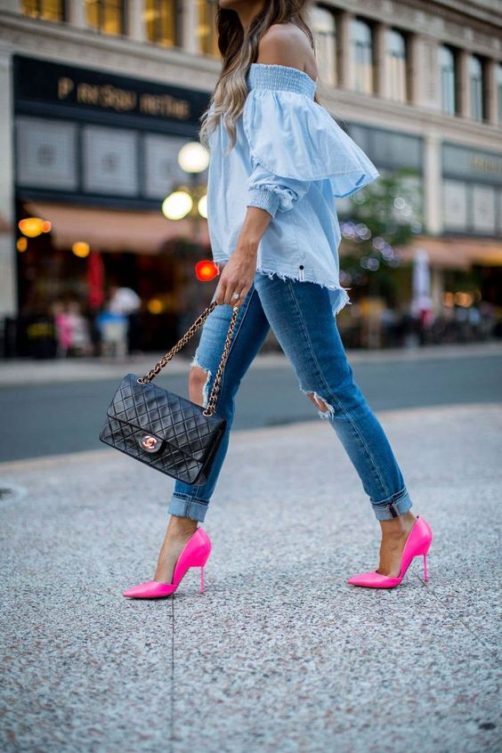 an off the shoulder blue shirt, blue ripped skinnies, neon pink shoes and a black bag