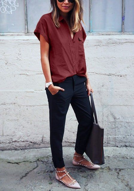 black pants, a burgundy straight button down with short sleeves, neutral studded shoes and a blakc tote