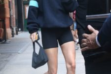07 a dark hoodie, black bike shorts, black booties and a black bag