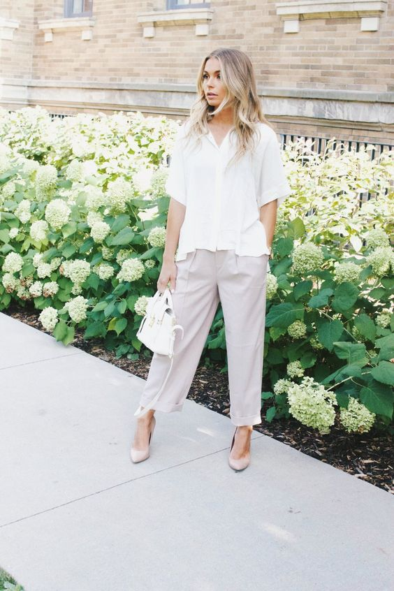 a relaxed summer outfit with a white button down with short sleeves, lavender pants and matching shoes and a white bag