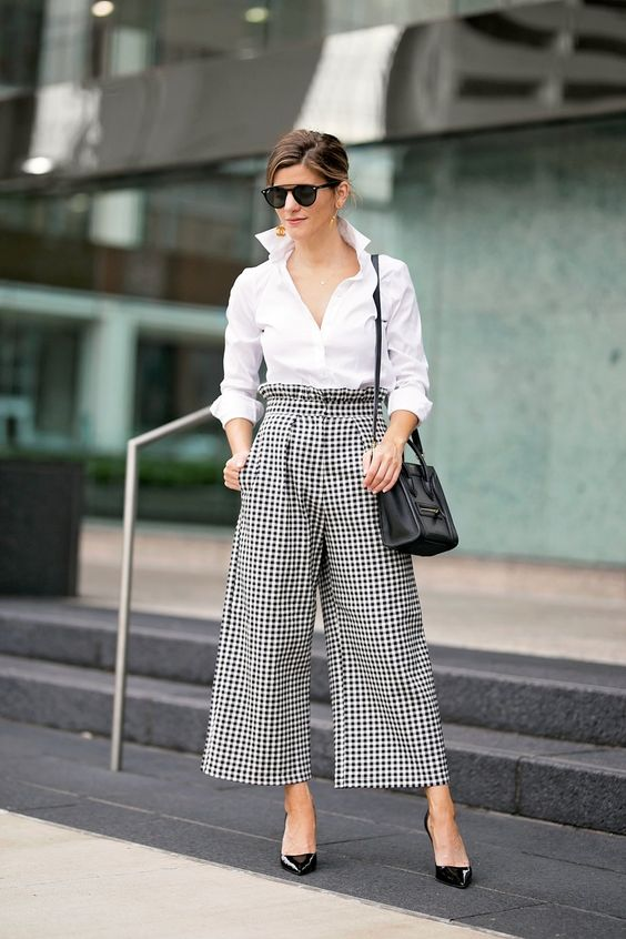 a white button down with long sleeves, gingham culottes, black heels and a black bag