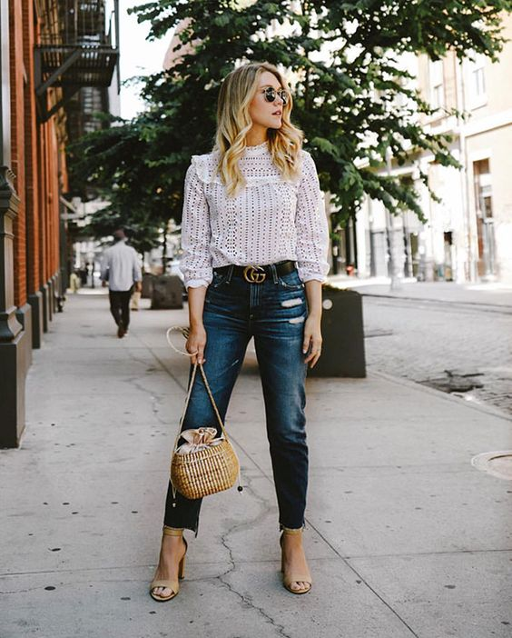 a white lace blouse with long sleeves and a turtleneck, blue mom jeans, nude shoes and a woven bag