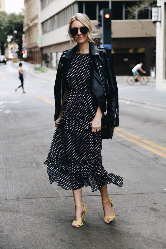 a black and white polka dot midi dress with ruffles and an accented waist, a black leather jacket and neon yellow heels