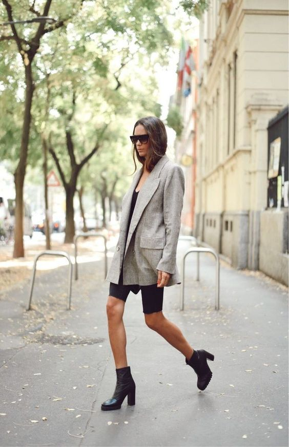 a black tee, black cycling shorts, black booties and a light grey oversized blazer by Victoria Beckham