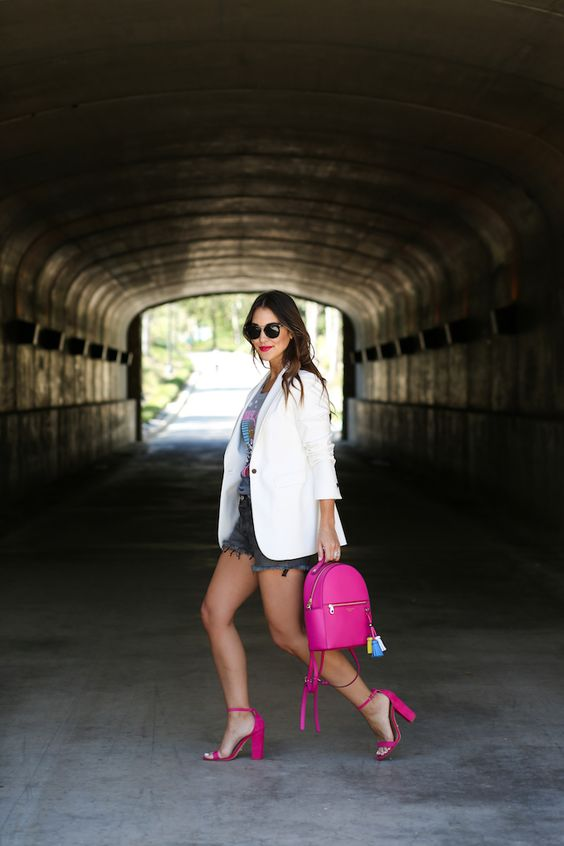 a graphic tee, grey denim shorts, a white blazer, neon pink heels and a matching backpack
