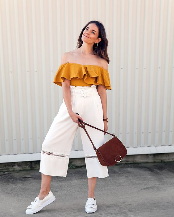 a mustard off the shoulder ruffle top, white culottes with a sheer insert, white loafers and a brown bag