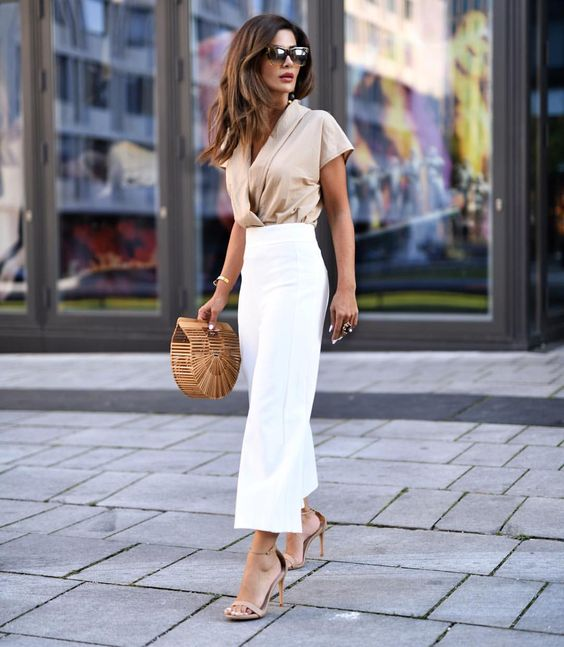 a tan silk blouse with a V-neckline, short sleeves, white wideleg pants, nude shoes and a wooden bag