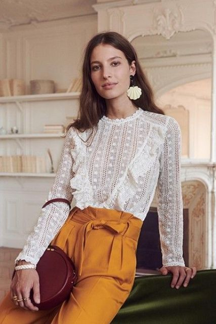 a white lace blouse with ruffles and long sleeves, mustard high waisted pants and a burgundy round bag