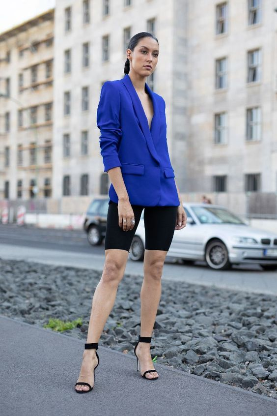 a bold blue oversized blazer, black bike shorts, black ankle strap shoes