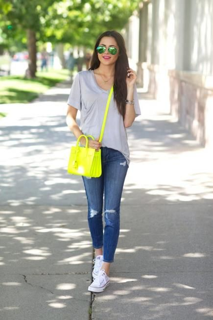 an oversized grey tee, blue ripped jeans, white sneakers, a neon yellow bag