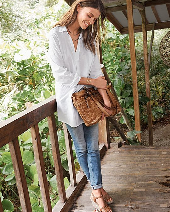 an oversized white shirt, blue skinnies, brown wedges and a brown leather bag