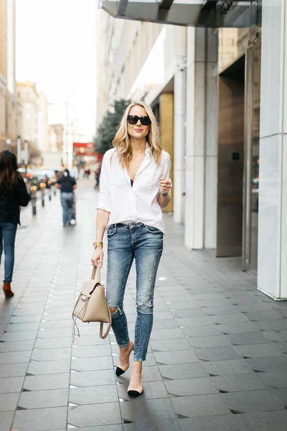 blue ripped jeans, a white shirt, a black bra under it, a nude bag and nude and black slingbacks