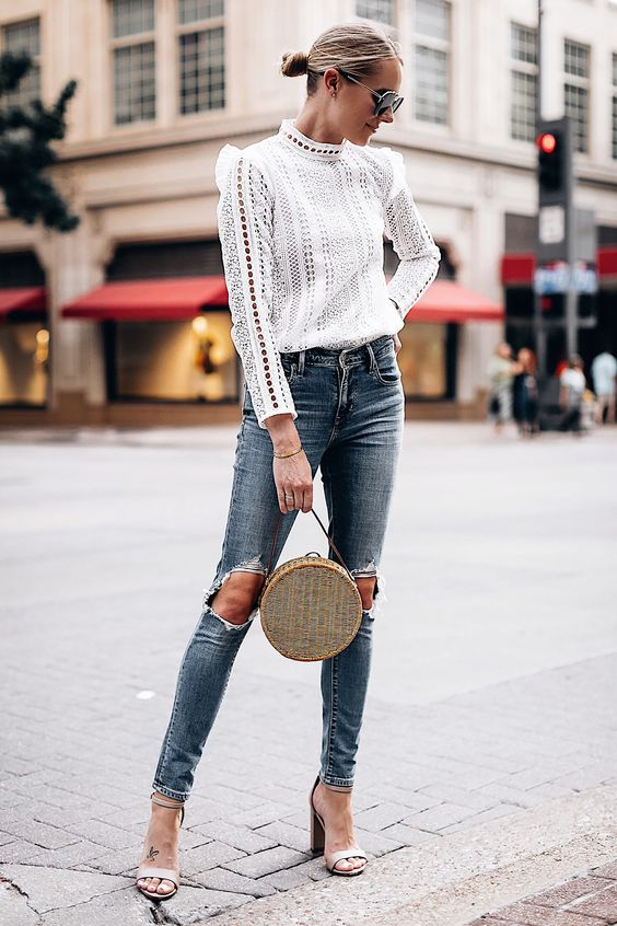 blue ripped skinnies, a white crochet lace blouse with a turtleneck and long sleeves, nude heels and a wicker round bag