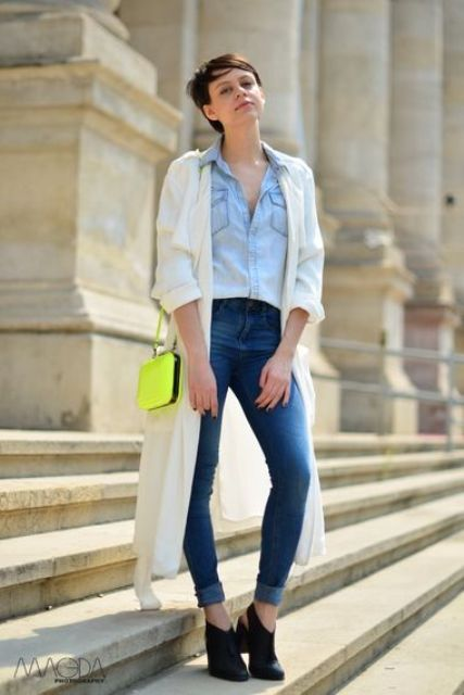 a chambray shirt, blue skinnies, black booties, a neutral duster and a neon yellow crossbody