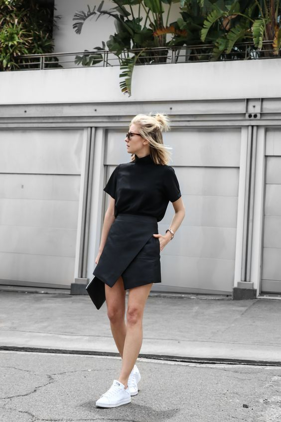 a modern look with a black turtleneck tee, black asymmetrical skirt and white sneakers