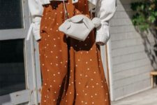 10 a rust and white polka dot midi dress, an oversized white denim jacket, rust-colored booties and a white bag